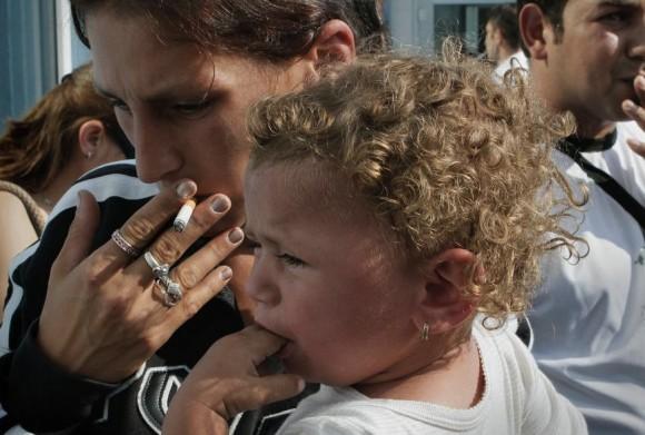 Mariana Sasz, con su hija en brazos, y su marido Ionut Sasz, fuman a su llegada a Bucarest tras ser deportados desde Francia.- AP