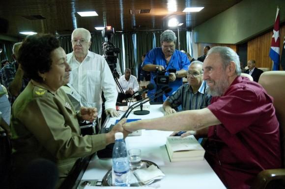 Tras dedicarle el libro, Fidel saluda a Teté Puebla. Al fondo, Armando Harta. Foto: Roberto Chile.