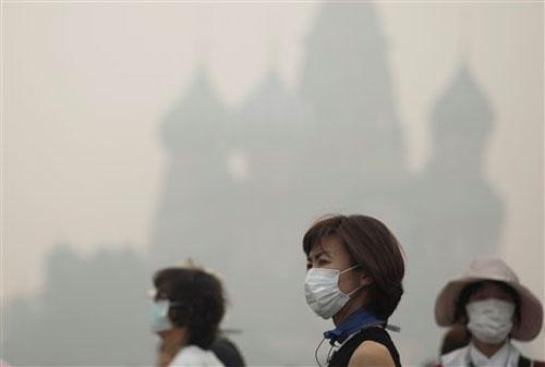 Turistas con máscaras tapabocas caminan por la Plaza Roja de Moscú en Rusia. El humo de los incendios forestales ha sofocado la ciudad. Foto tomada el lunes 9 de agosto del 2010. (Foto AP/Alexander Zemlianichenko)