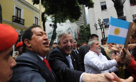 El presidente venezolano, Hugo Chávez, junto al secretario general de Unasur, Néstor Kirchner, y el presidente brasileño, Luiz Inácio Lula da Silva, saludan al pueblo venezolano, en la Plaza Bolívar en Caracas, el 6 de agosto de 2010. AIN FOTO/TELAM