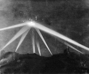 Distintos focos direccionales de búsqueda de aviones iluminando el contorno de una nube. Los puntos blancos eran las explosiones causadas por las municiones con cabeza explosiva utilizadas