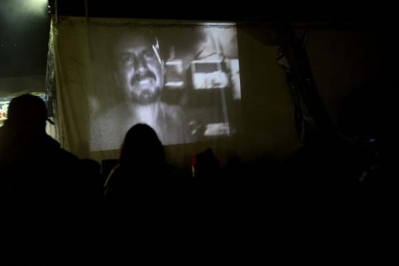 Familiares observan el vídeo logrado por los equipos enviados por el Gobierno hoy, jueves 26 de agosto de 2010, en el lugar donde se encuentran atrapados desde el pasado 5 de agosto los 33 mineros, a 700 metros bajo tierra, en el yacimiento San José, cerca a Copiapó, norte de Chile. La grabación, hecha por uno de los obreros atrapados, dura unos 45 minutos y fue exhibida en más de alguna oportunidad en una gran pantalla que se levantó en las cercanías de lo que fue la entrada del yacimiento con el fin de que sus familiares lo pudieran ver y también grabar. EFE/Esteban González