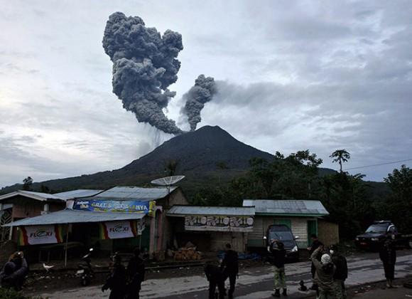 Un residente de la ciudad de Medan escapa de su vivienda hoy, lunes 30 de agosto de 2010, después de que el volcán Monte Sinabung, situado al norte de la isla indonesia de Sumatra, entró en erupción por segunda vez en 24 horas tras pasar dormido los últimos 400 años, informó el Centro de Vulcanología de Indonesia. Más de 20.000 personas continúan realojadas en los centros de evacuación desde el domingo ante el estado de alerta por el volcán, que esta madrugada lanzó una columna de humo y ceniza de dos kilómetros de alto. EFE/ADE SAHPUTRA
