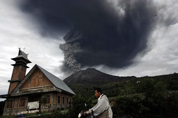 Foto: Residentes de la ciudad de Medan observan hoy, lunes 30 de agosto de 2010, el volcán Monte Sinabung, situado al norte de la isla indonesia de Sumatra, que entró en erupción por segunda vez en 24 horas tras pasar dormido los últimos 400 años, informó el Centro de Vulcanología de Indonesia. Más de 20.000 personas continúan realojadas en los centros de evacuación desde el domingo ante el estado de alerta por el volcán, que esta madrugada lanzó una columna de humo y ceniza de dos kilómetros de alto. EFE/ADE SAHPUTRA