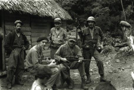 De pie, de izquierda a derecha, los combatientes rebeldes: Ignacio Leal Díaz, Ciro Redondo y Camilo Cienfuegos; sentados sobre unas piedras: Marcelo Fernández Font y el Comandante Fidel Castro.