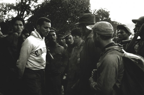 Rodeado por los guerrilleros, el cadete Evelio Laferté, prisionero de las tropas rebeldes, responde a las preguntas del Che.