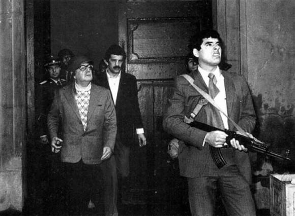 """Allende viste una chaqueta y un pantalón marengo. Carga con un fusil AK-47 Kalashnikov, regalo de Fidel Castro, y el GAP ingresa al palacio de gobierno dos ametralladoras y tres RPG-7, además de sus armas personales...Allende trata de obtener información sobre el movimiento, al no poder contactar a Pinochet exclama, """"Pobre Pinochet, debe estar preso""""."""
