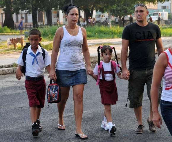 Los padres llevan a los niños pequeños a la escuela. Foto: AFP