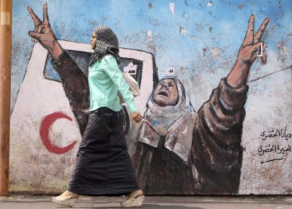 Una mujer palestina pasa frente a un muro en Gaza. Foto: Reuters