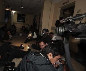 Miembros de la prensa nacional e internacional se protegen en el piso del fuego cruzado mientras militares sacan hoy, jueves 30 de septiembre de 2010, al presidente de Ecuador, Rafael Correa (c) del hospital donde se encontraba retenido. Fuerzas militares liberaron al mandatario, tras un enfrentamiento contra los policÌas sublevados que lo mantenÌan recluido en el centro hospitalario. Desde allÌ, Correa se trasladÛ al Palacio de Carondelet, la sede del Ejecutivo, y se asomÛ al balcÛn, donde le esperaban algunos ministros, para dirigirse a centenares de sus partidarios congregados en la Plaza Grande y que ondeaban banderas de Ecuador. EFE/JosÈ Jacome