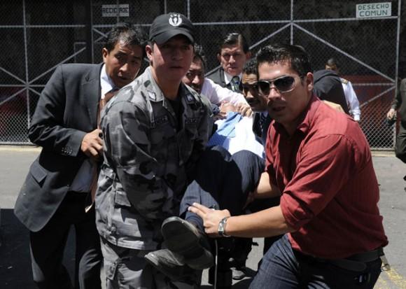 Rafael Correa es cargado del Regimiento Quito luego de ser alcanzado por las bombas de gas. AFP PHOTO / RODRIGO BUENDIA