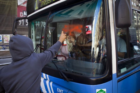 En la Gran Vía de Madrid, un manifestante pinta el parabrisas de un ómnibus.