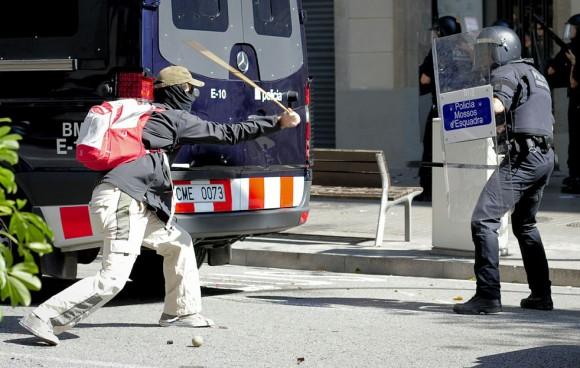 Un manifestante se enfrenta a la policía en Barcelona.