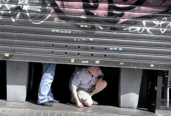 Un hombre observa a los huelguistas mientras cierra una tienda de Barcelona