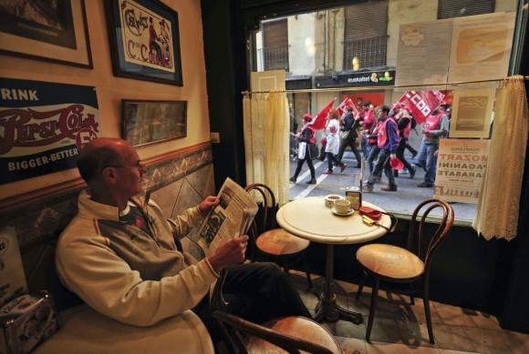Un hombre en un café de Pamplona, en el norte de España, ve el paso de los huelguistas.
