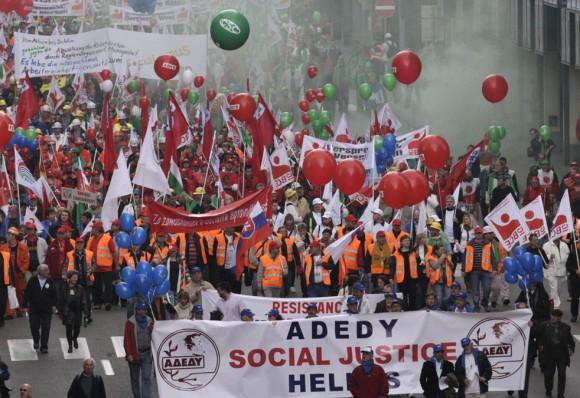 Los manifestantes de una marca griega de la Unión tienen una bandera, ya que marchan por una avenida principal en Bruselas, el Miércoles, 29 de septiembre 2010.