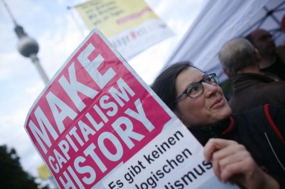 """Un manifestante sostiene un cartel durante una manifestación sindical contra los recortes presupuestarios, en Berlín, Miércoles, 29 de septiembre 2010. Varios cientos de manifestantes marcharon en Berlín en una de las muchas manifestaciones que tuvieron lugar en toda Europa para protestar contra los planes de austeridad del gobierno destinadas a reducir los déficits. El cartel dice: """"Hacer la historia del capitalismo - No hay capitalismo ecológico"""""""