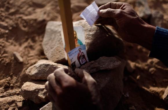 Carlos Araya coloca la imagen de San Expedito, junto a una bandera chilena con el nombre de un familiar, uno de los 33 mineros atrapados en la mina San José, el 23 de agosto 2010. (Foto AP / Roberto Candia)