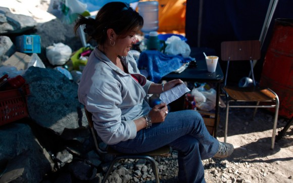 Carola Narváez, esposa de Raúl Bustos, uno de los mineros atrapados en la mina San José, lee una carta de su esposo dirigida,  26 de agosto 2010. Narváez y su esposo también son sobrevivientes del terremoto de febrero en Chile. (Foto AP / Natacha Pisarenko)