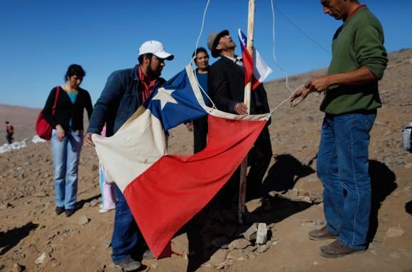 Familiares de los mineros atrapados Renan y Florencio Avalo levantan una bandera chilena hecha jirones en una colina con vistas al campo, donde las familias de los mineros atrapados esperan fuera de la mina San José. Es el sábado 28 de agosto 2010. Esta bandera se convirtió en un símbolo de la resistencia en Chile cuando un sobreviviente del terremoto fue fotografiado sacándola de los escombros del terremoto y el tsunami del 27 de febrero. (Foto AP / Roberto Candia)