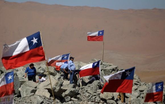 Los familiares de los mineros atrapados conviven entre banderas chilenas fuera de la mina el domingo 29 de agosto 2010. (Foto AP / Roberto Candia)