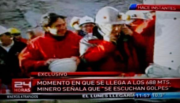 El ministro de Minería de Chile, Laurence Golborne, izquierda, sonríe junto a un funcionario no identificado tras escuchar sonidos desconocidos procedentes de la zona donde la mina se derrumbó. Los 33 mineros llevan 17 días atrapados en Copiapó, Chile, Domingo, 22 de agosto 2010. (Foto AP)