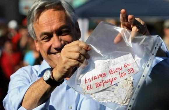 """El Presidente de Chile, Sebastián Piñera muestra un mensaje que dice """"Estamos bien en el refugio los 33"""", de los mineros atrapados, el 22 de agosto de 2010. Los mineros están vivos. Se establece contacto con ellos 17 días después que un colapso estructural los atrapó bajo tierra. (RETAMAL HECTOR / AFP / Getty Images)"""