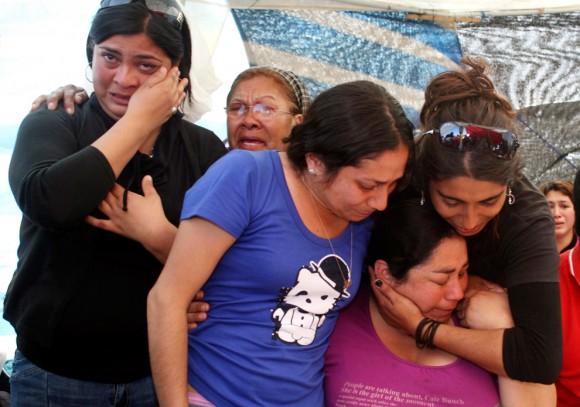 Los familiares de los mineros atrapados reaccionan al enterarse de que los 33 mineros fueron encontrados con vida el 22 de agosto de 2010. (REUTERS / Retamal Hector)