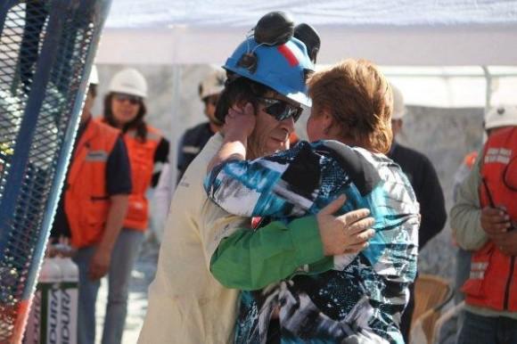 El minero Johnny Barrios (i), de 50 años, saluda a su pareja al llegar a la superficie a bordo de la cápsula Fénix 2.