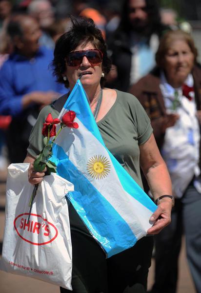 Una mujer portando dos rosas rojas y una bandera argentina, entra por el pasillo armado con vallas, que conduce a la sala de la Casa de Gobierno, donde le dan el último adios al ex presidente Néstor Kirchner, en Argentina, el 28 de octubre de 2010. AIN FOTO/ Paula RIBAS/TELAM