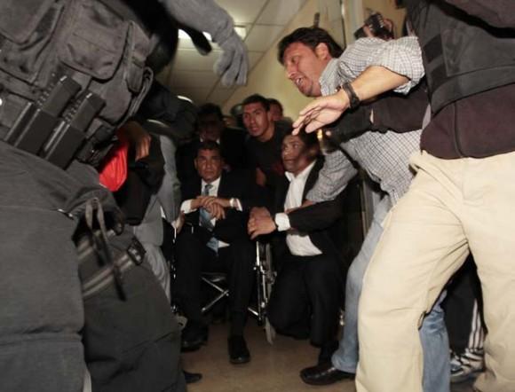 Militares sacan hoy, jueves 30 de septiembre de 2010, al presidente de Ecuador, Rafael Correa (c) del hospital donde se encontraba retenido. Fuerzas militares liberaron al mandatario, tras un enfrentamiento contra los policías sublevados que lo mantenían recluido en el centro hospitalario. Desde allí, Correa se trasladó al Palacio de Carondelet, la sede del Ejecutivo, y se asomó al balcón, donde le esperaban algunos ministros, para dirigirse a centenares de sus partidarios congregados en la Plaza Grande y que ondeaban banderas de Ecuador. EFE/José Jacome