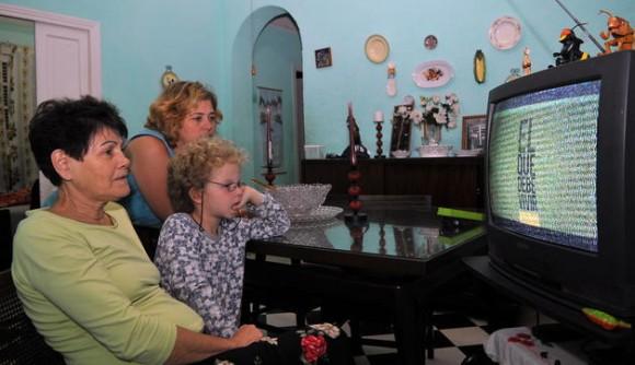 """Dos mujeres y un niño observan hoy, domingo 7 de marzo del 2010, en La Habana, en el horario estelar de la televisión estatal cubana, la serie """"El que debe vivir"""", un dramatizado de ocho capítulos con conocidos actores de la isla sobre algunos de los 638 atentados planeados en el último medio siglo contra el líder de la revolución de 1959, Fidel Castro. EFE/Stringer"""