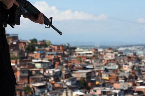 Dos policías patrullan una calle de la favela Grota mientras un hombre asea el frente de una casa hoy, lunes 29 de noviembre de 2010, un día después de que las fuerzas de seguridad tomaran varias barriadas en Río de Janeiro (Brasil). Parte de los soldados del Ejército que el domingo ayudaron a ocupar un conjunto de favelas, que eran controladas por el narcotráfico, permanecerá en el lugar entre seis y siete meses. EFE/FERNANDO BIZERRA JR