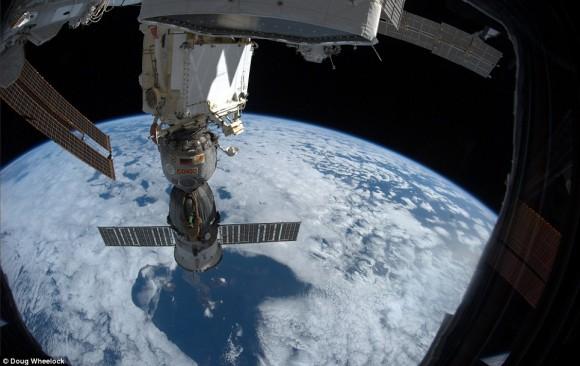 Único momento surrealista en el espacio: Desde la cúpula, una vista de la Soyuz TMA-19 'de Olympus, la nave espacial que llevará a casa el Comandante Wheelock. Las Islas Galápagos se pueden ver a través de una ruptura en las nubes por debajo de