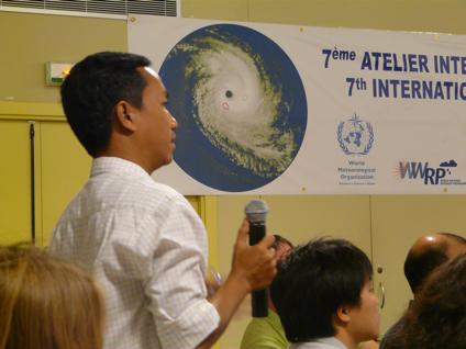 Pronosticador de la zona del océano ĺndico hace uso de la palabra en las sesiones del IWTC-7. Obsérvese la imagen del huracán al fondo, los vientos giran al revés que en en los del el hemisferio norte.