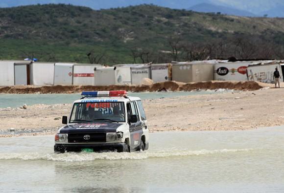Una patrulla de la Policía Nacional Haitiana cruza por un arroyo, en el puesto fronterizo de Malpase (Haití), límite con República Dominicana. El crecimiento del lago Azuei y las lluvias del huracán Tomás, mantienen inundadas las oficinas policiales de ambos países. EFE/Orlando Barría