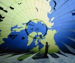Un activista de Greenpeace mira un globo de aire caliente antes del comienzo de la cumbre climática de las Naciones Unidas en Cancún. Fotografía: Luis Pérez / AFP / Getty Images