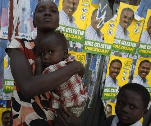 Una mujer con sus dos hijos frente a una pared en Petionville, Puerto Príncipe, con carteles alusivas a las elecciones. Foto: Reuters