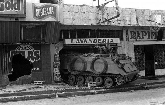 Un Ejército de los EE.UU. M-113 de transporte de personal blindados guardias de una calle cerca del edificio destruido la sede de la Fuerza de Defensa de Panamá durante el segundo día de la Operación Causa Justa.