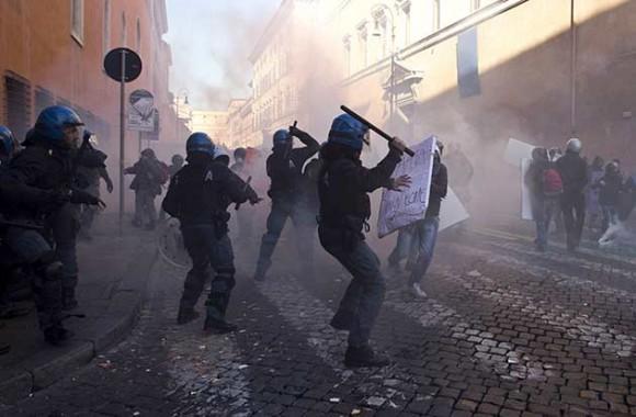 Foto: Agentes de la Policía italiana cargan contra los manifestantes que protestaron contra el Gobierno de Silvio Berlusconi, durante los duros enfrentamientos ocurridos ante la sede del Senado y la plaza Venecia, en el centro de Roma (Italia), hoy, martes 14 de diciembre de 2010. Los agentes cargaron duramente contra varios centenares de estudiantes que intentaron atravesar el cordón policial instalado en torno al Palacio Madama, sede del Senado, después de que éstos lanzaran piedras, petardos, botes de humo y pintura contra la sede de la cámara alta. Miles de personas se manifiestaron hoy en las principales ciudades de Italia para protestar contra el Gobierno de Silvio Berlusconi, quien se juega su futuro en la Cámara de los Diputados, donde su Ejecutivo afronta dos mociones de censura. EFE/MASSIMO PERCOSSI