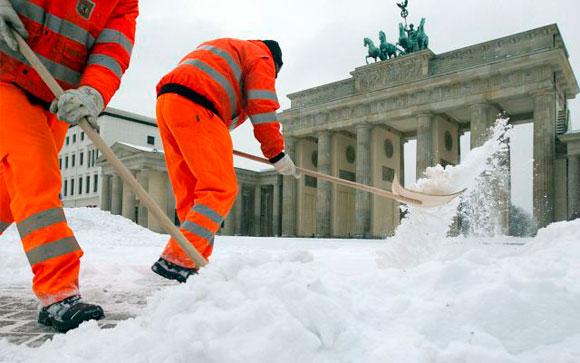 ALEMANIA.- Trabajadores de limpieza de la ciudad de Berlín retiran la nieve recién caída frente a la Puerta de Brandenburgo. Foto: AP/Gero Breloer