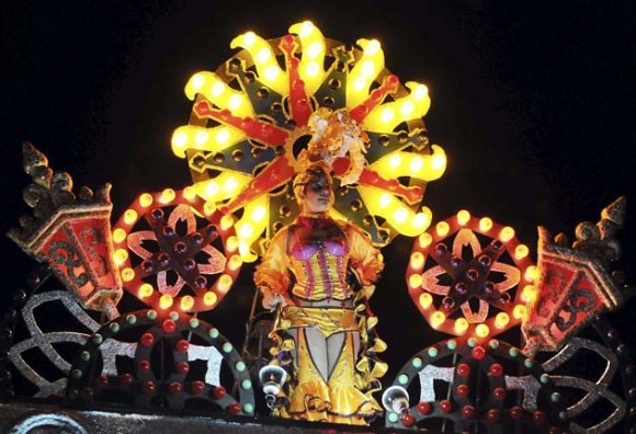 """MAYABEQUE (CUBA) 02/01/11.- Una chica baila en la carroza Espina de Oro que participa, hoy domingo 02 de enero, en la fiesta conocida como """"las Charangas de Bejucal"""", una mezcla de carnaval, baile y espectáculo de magia que se considera como una de las tradiciones populares más antiguas de la isla. La gran atracción de la fiesta consiste en presenciar las """"sorpresas"""" que van revelando las carrozas de cada bando, ubicadas en extremos opuestos de la plaza, donde el público asiste a la transformación de un cajón rodante en un edificio de luces y color de casi 20 metros. EFE/Alejandro Ernesto"""