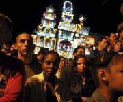 """MAYABEQUE (CUBA) 02/01/11.- Varias personas disfrutan del desfile de las carrozas Ceiba de Plata (al fondo) y Espina de Oro, que participan, hoy domingo 02 de enero, en la fiesta conocida como """"las Charangas de Bejucal"""", una mezcla de carnaval, baile y espectáculo de magia que se considera como una de las tradiciones populares más antiguas de la isla. La gran atracción de la fiesta consiste en presenciar las """"sorpresas"""" que van revelando las carrozas de cada bando, ubicadas en extremos opuestos de la plaza, donde el público asiste a la transformación de un cajón rodante en un edificio de luces y color de casi 20 metros. EFE/Alejandro Ernesto"""