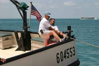 """Miembros de la tripulación cubano estadounidense del """"Santrina"""", con licencia de Estados Unidos no. 604553, y portando la bandera estadounidense, tratan de sacar su bote a seguro. Foto: D.R. 2005 Mario Alonzo, Por Esto!"""