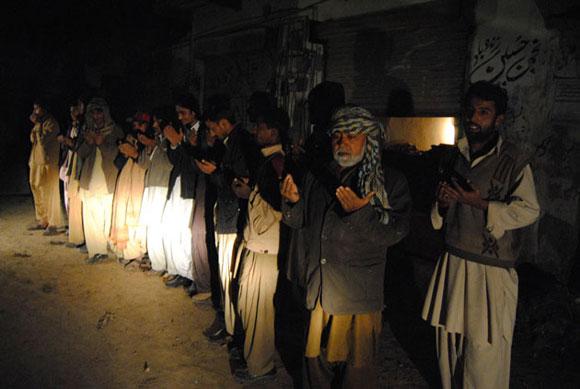 Habitantes de Jafarabad, 300 kilómetros al norte de Quetta, Pakistán, oran frente a sus viviendas después que un potente terremoto sacudió el área en la madugada del miércoles del 19 de enero del 2010. Un potente sismo de 7,2 grados de magnitud sacudió el suroeste de Pakistán y provocó temblores en la India, Afgnistán y Emiratos Arabes. Foto: AP/Fida Hussain