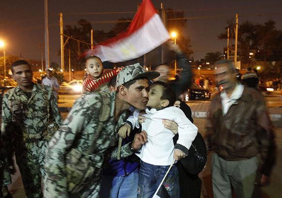Un niño egipcio besa a un soldado mientras el pueblo celebra en la Plaza Tahrir. Foto:Mohammed Abed/AFP/