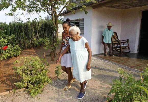 En esta foto del 4 de febrero del 2010, Juana Bautista de la Candelaria Rodríguez es ayudada por su nieta Martarita Cabrera en su casa cerca de Campechuela, en la región de la provincia de Granma en donde nació al este de Cuba. Bautista, quien también es conocida como Candulia, nació en 1885 según el registro civil y celebró 125 años el 2 de febrero, con lo cual se convertiría en la persona más vieja del mundo. Un vocero de los récords Guiness dijo la AP que no estaban enterados del caso de Bautista.  (AP Foto/Ismael Francisco, Prensa Latina)