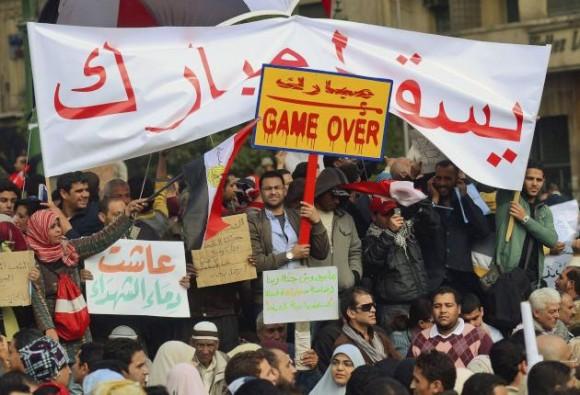 Un manifestante (c) sostiene una pancarta donde se lee 'Se acabó el juego', durante una masiva protesta convocada por el movimiento opositor para exigir la dimisión del presidente Hosni Mubarak, en la plaza Tahrir (plaza de la Liberación) en El Cairo, Egipto, hoy, martes 01 de febrero de 2011. EFE/HANNIBAL HANSCHKE