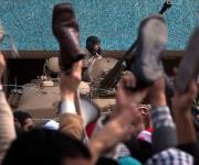 Durante el discurso de Mubarak, los protestantes alzan sus zapatos en señal de ofensa al presidente egipcio. Foto: Boston Globe