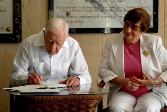 James Carter firma el libro de visitas de la sinagoga habanera Bet Shalom. A su lado Adela Dworin. Foto: Marcelino Vázquez Hernández